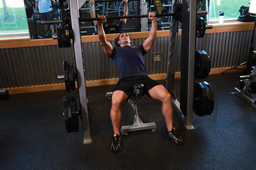 Подъем плеч на наклонной скамье в тренажере Смита